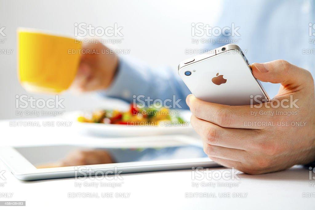 Man using iPhone and iPad royalty-free stock photo