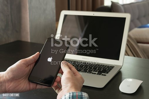 BANGKOK, THAILAND - NOVEMBER 26, 2016: Man using Iphone7 Plus jet black serie on opening screen of Apple inc. icon with macbook air