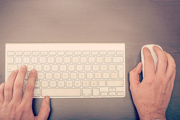 Man using keyboard and mouse stock photo