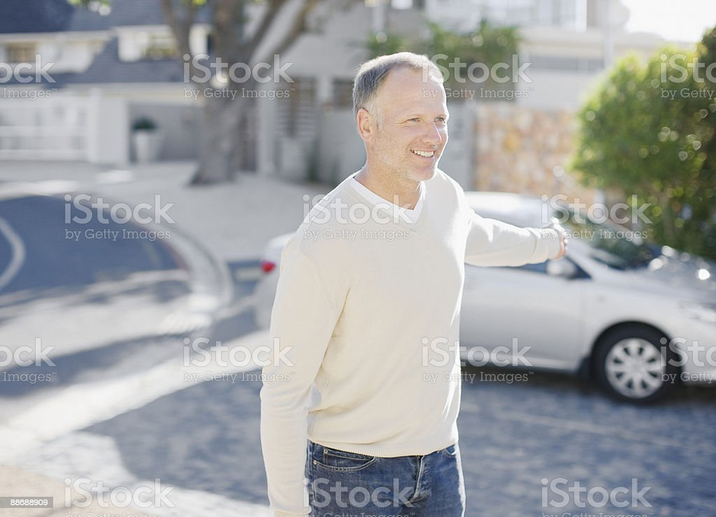 Man using keyless lock on car in driveway royalty-free stock photo