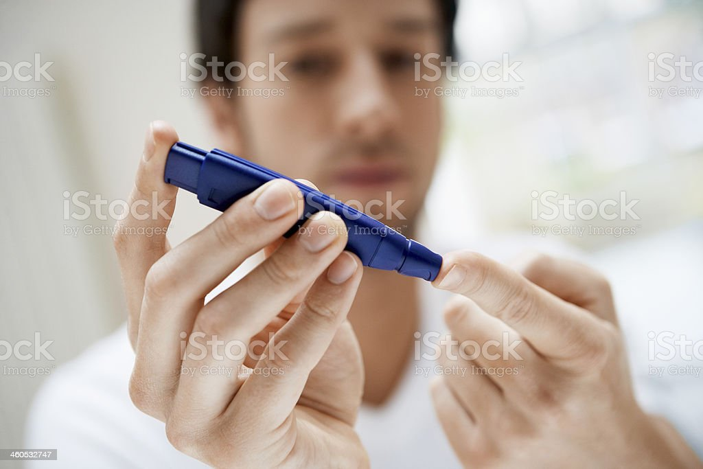 Man Using Lancelet On Finger In Bathroom stock photo