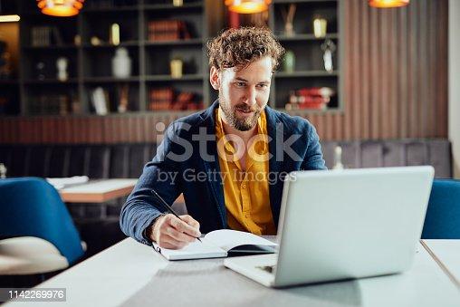 istock Man using lapotop in cafe. 1142269976