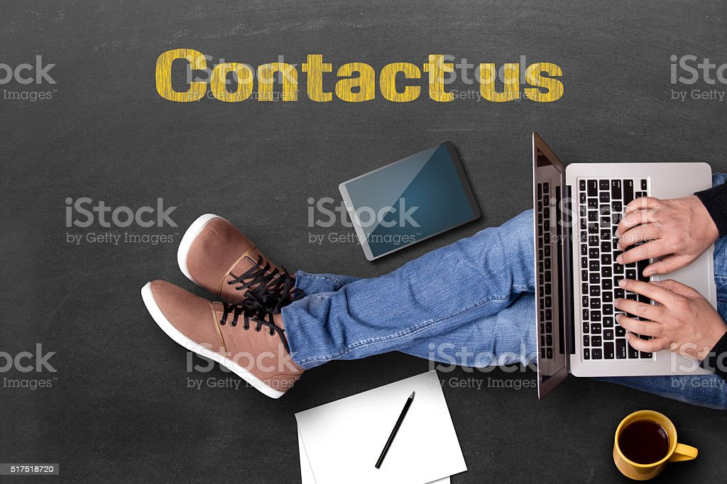Man using laptop and contact us written on blackboard stock photo