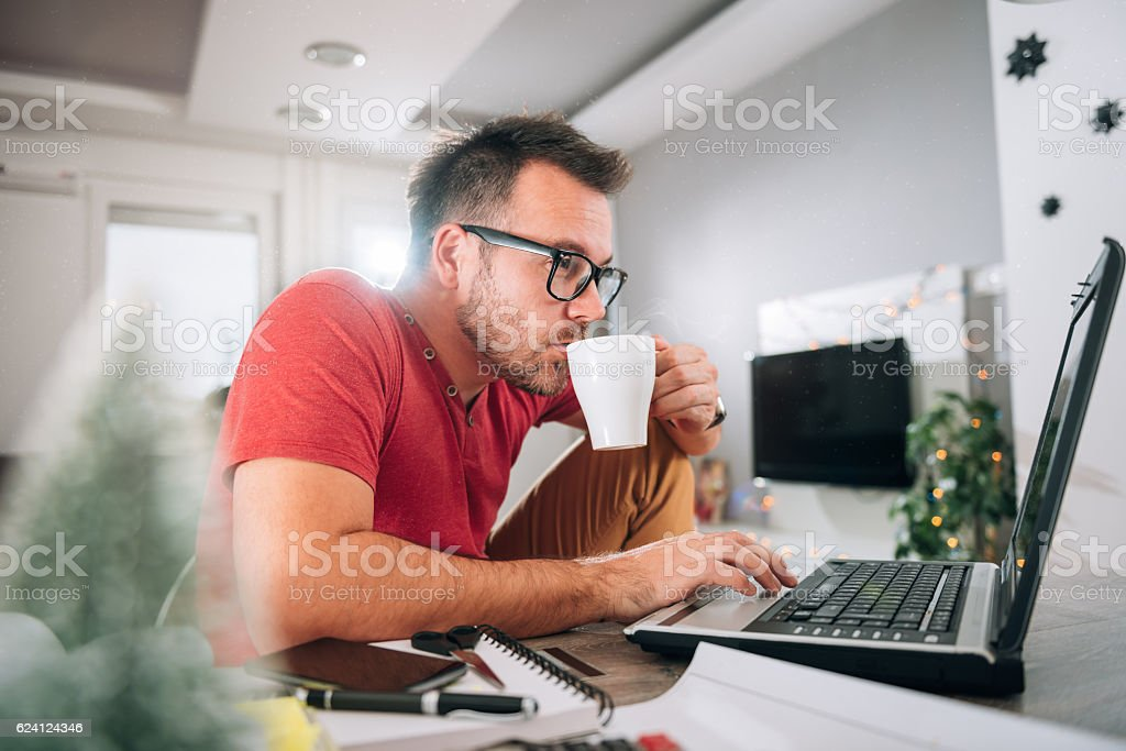 Man using laptop and drinking coffee stock photo