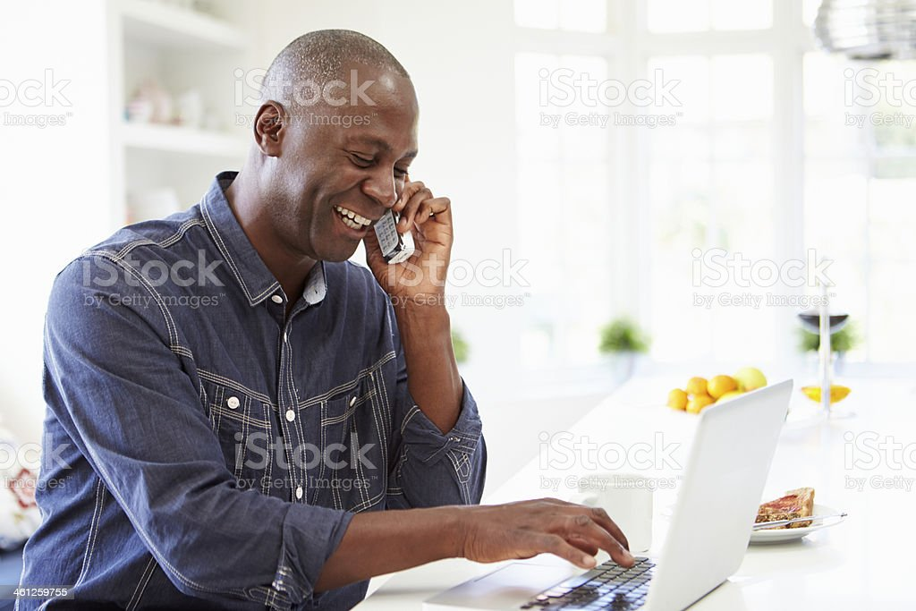 Man Using Laptop And Talking On Phone At Home stock photo