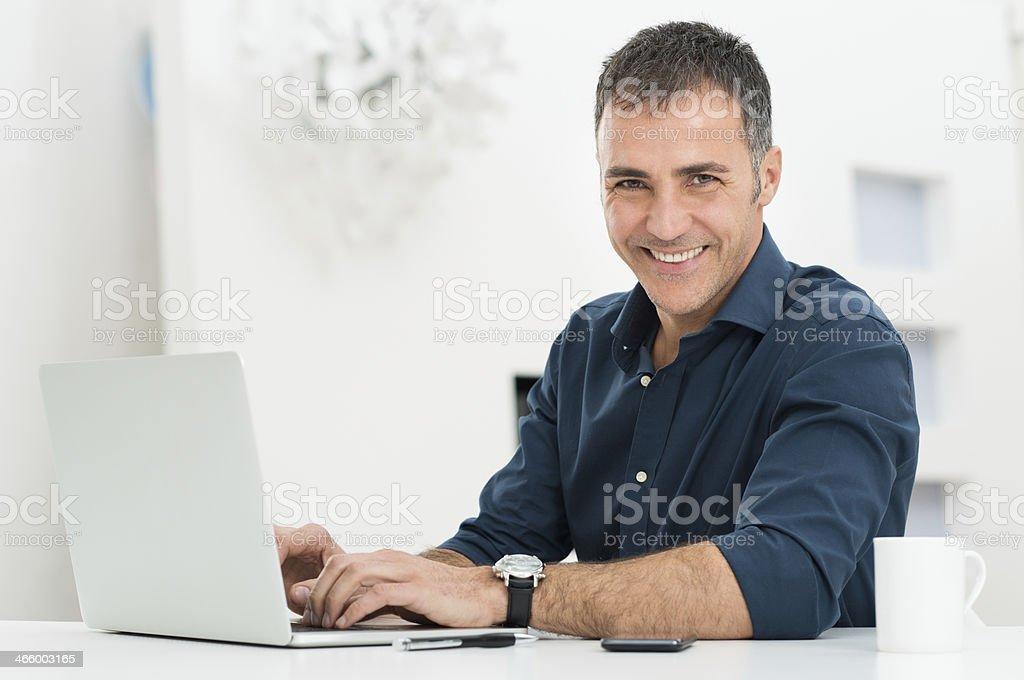 Man Using Laptop At Desk stock photo