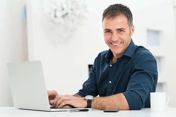 man using laptop at desk - mid volwassen mannen stockfoto's en -beelden