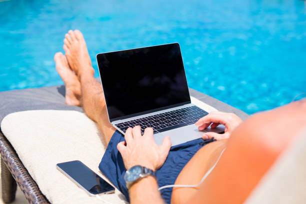 mann mit laptop-computer am pool. - traum pools stock-fotos und bilder