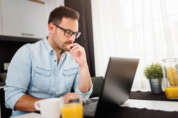 hombre con ayuda de ordenador portátil, trabajando en casa. preocupado por las finanzas. - accesorio financiero fotografías e imágenes de stock