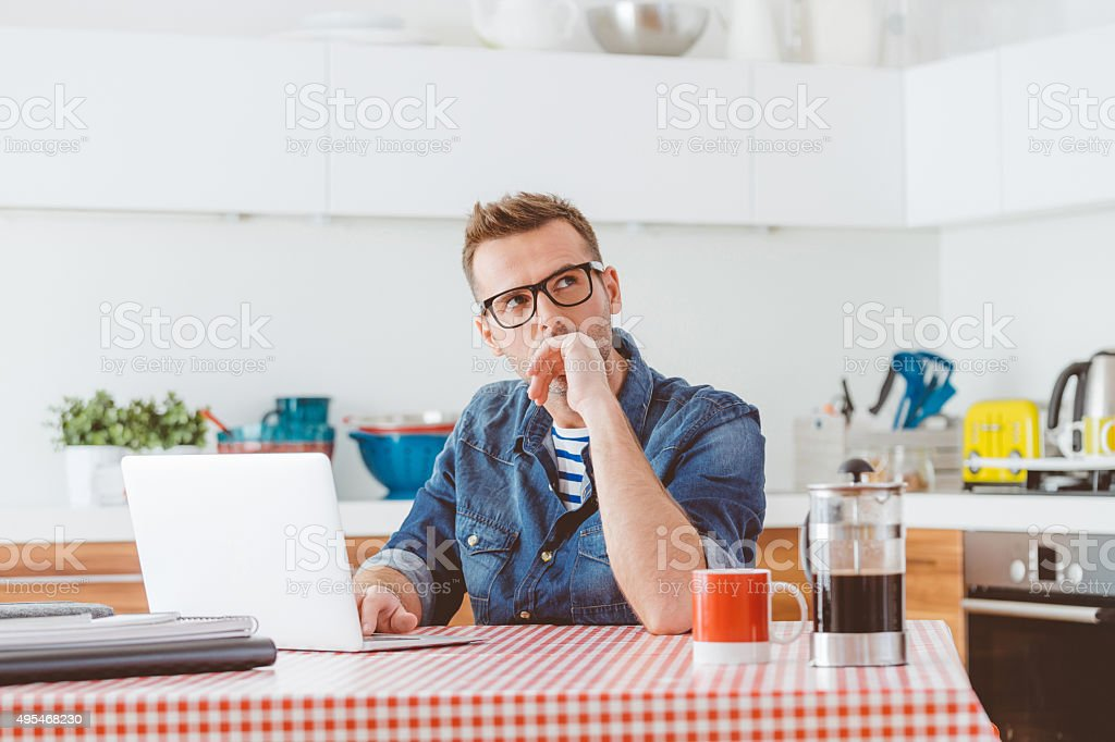 Man using laptop in a domestic kitchen stock photo