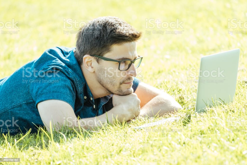 Man using laptop in city park lying on grass royalty-free stock photo