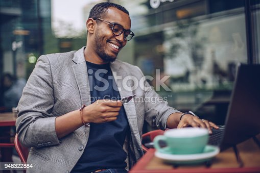 Attractive young man sitting in coffee shop and using laptop computer