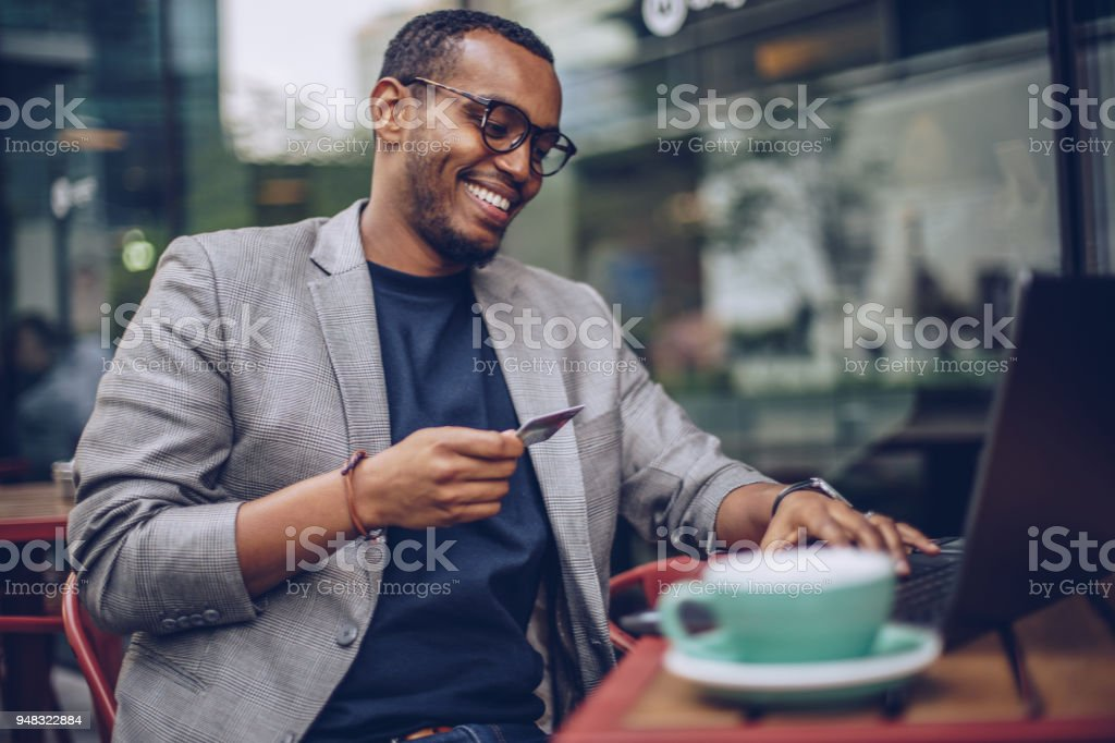 Man using laptop in coffee shop stock photo