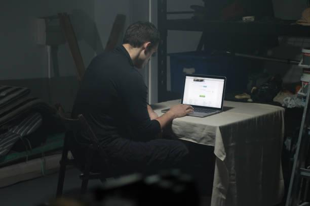 Man using laptop in dark room. stock photo
