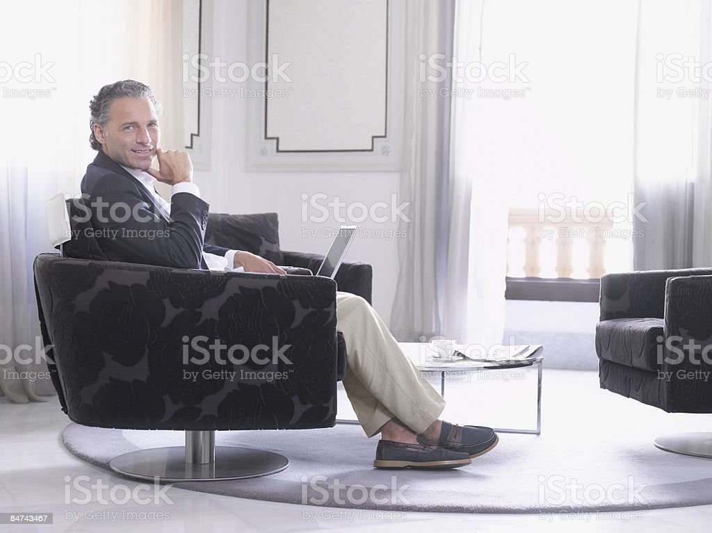 Man using laptop in modern hotel suite  royalty-free stock photo