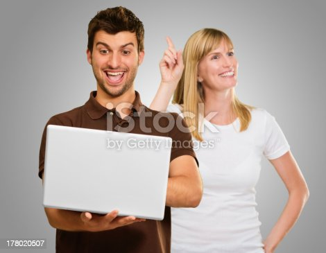 Man Using Laptop Infront Of Happy Woman Gesturing On Gray Background