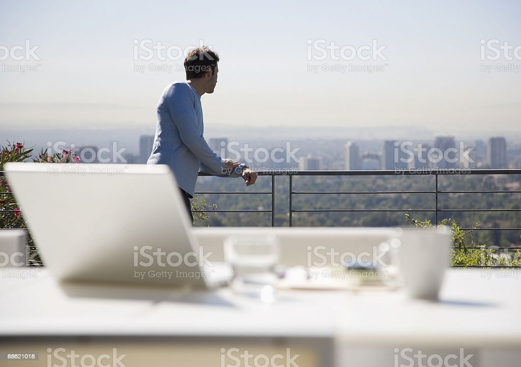 Man using laptop on balcony overlooking city stock photo