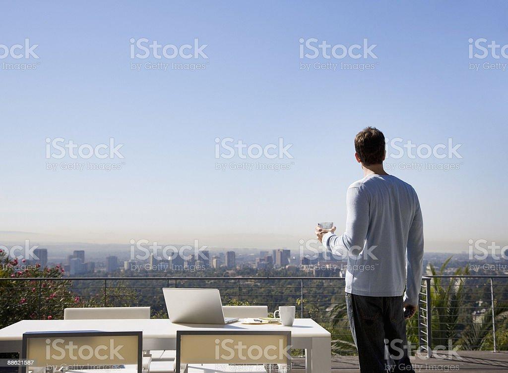 Homem usando o laptop na sacada com vista para a cidade - foto de acervo