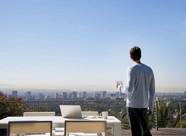 Man using laptop on balcony overlooking city stock photo