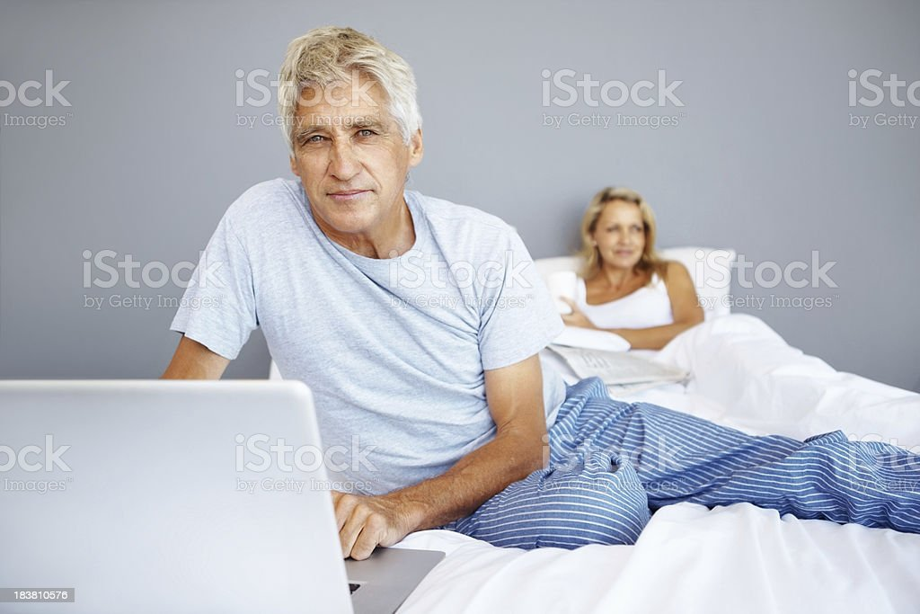 Man using laptop on bed royalty-free stock photo