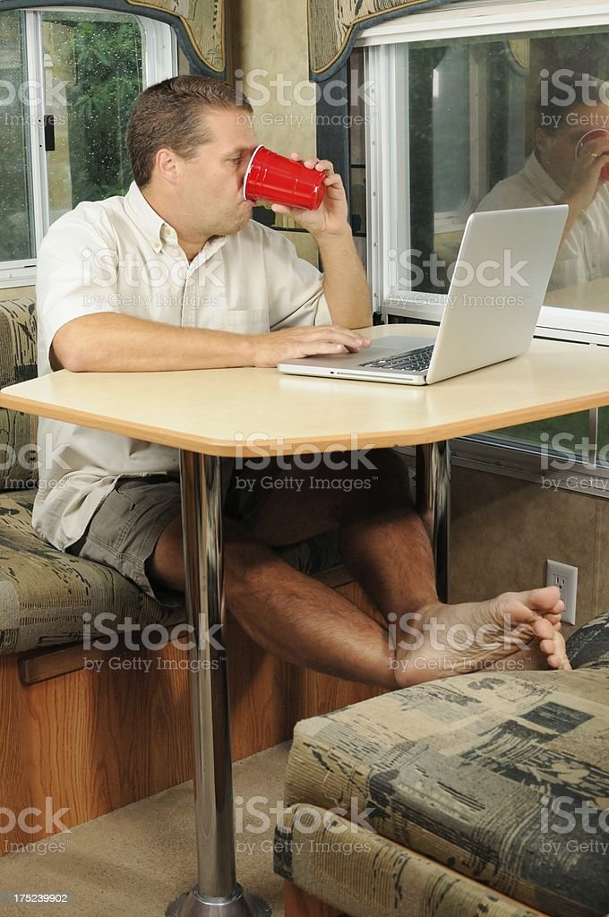 Man using laptop on RV dining table royalty-free stock photo