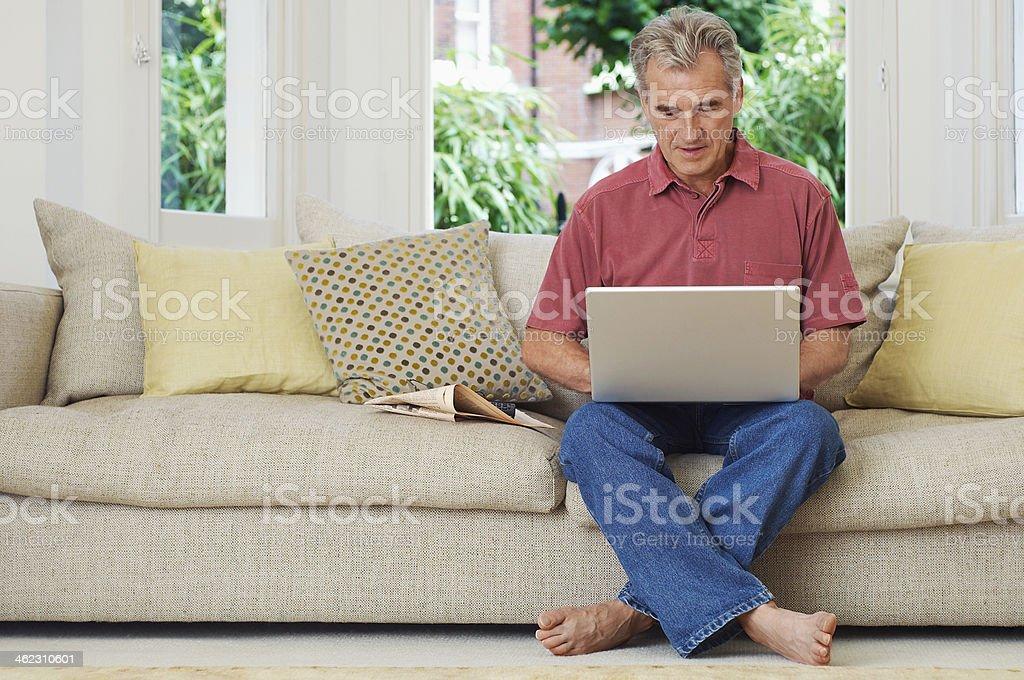 Mann mit Laptop auf Couch – Foto