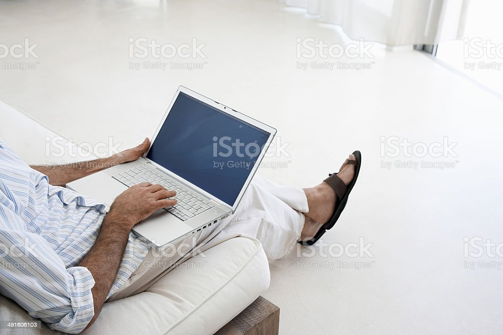 Man Using Laptop On Sofa royalty-free stock photo