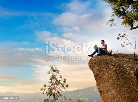 istock A man using laptop on the rock 846006730