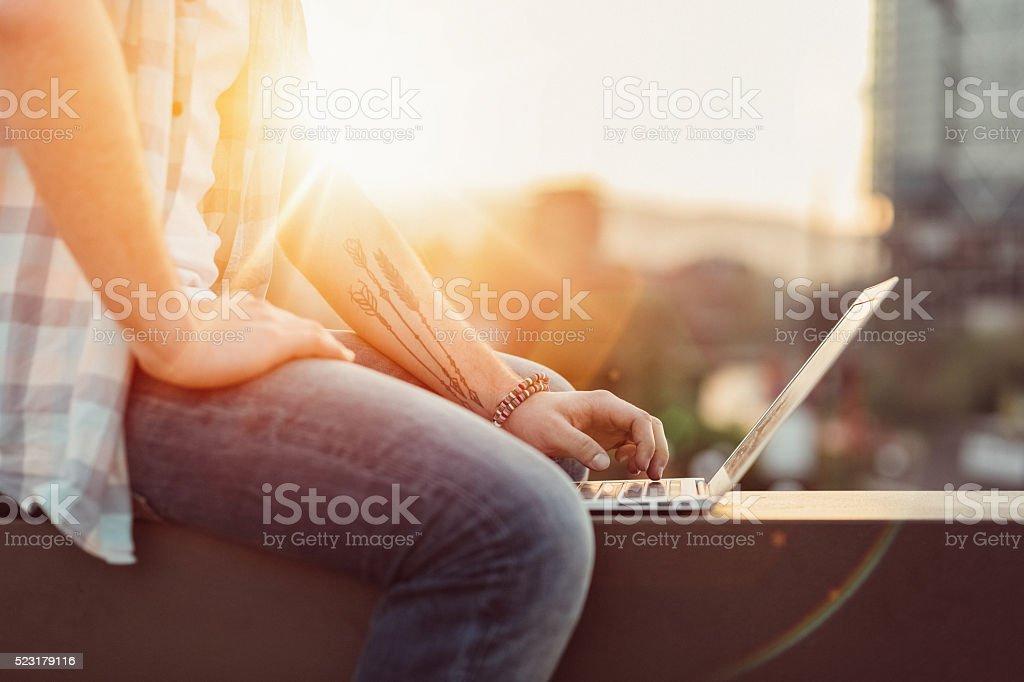 Man using laptop outside stock photo