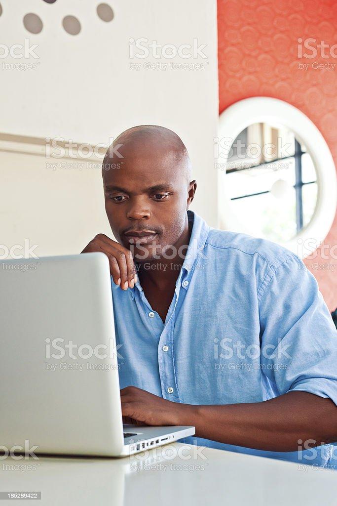 Man using laptop African man using laptop at home. Adult Stock Photo