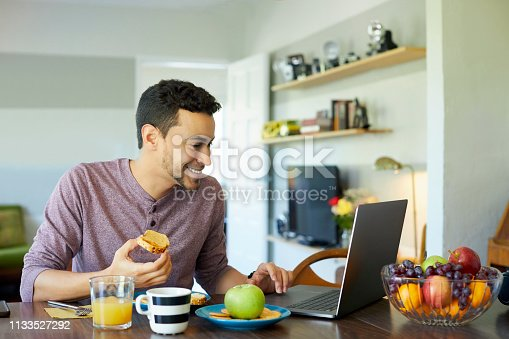 Smiling young man using laptop at dining table. Male is having breakfast at home. He is enjoying social media and meal.