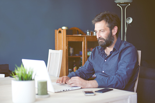 Man Using Laptop While Working From Home Stock Photo - Download Image Now