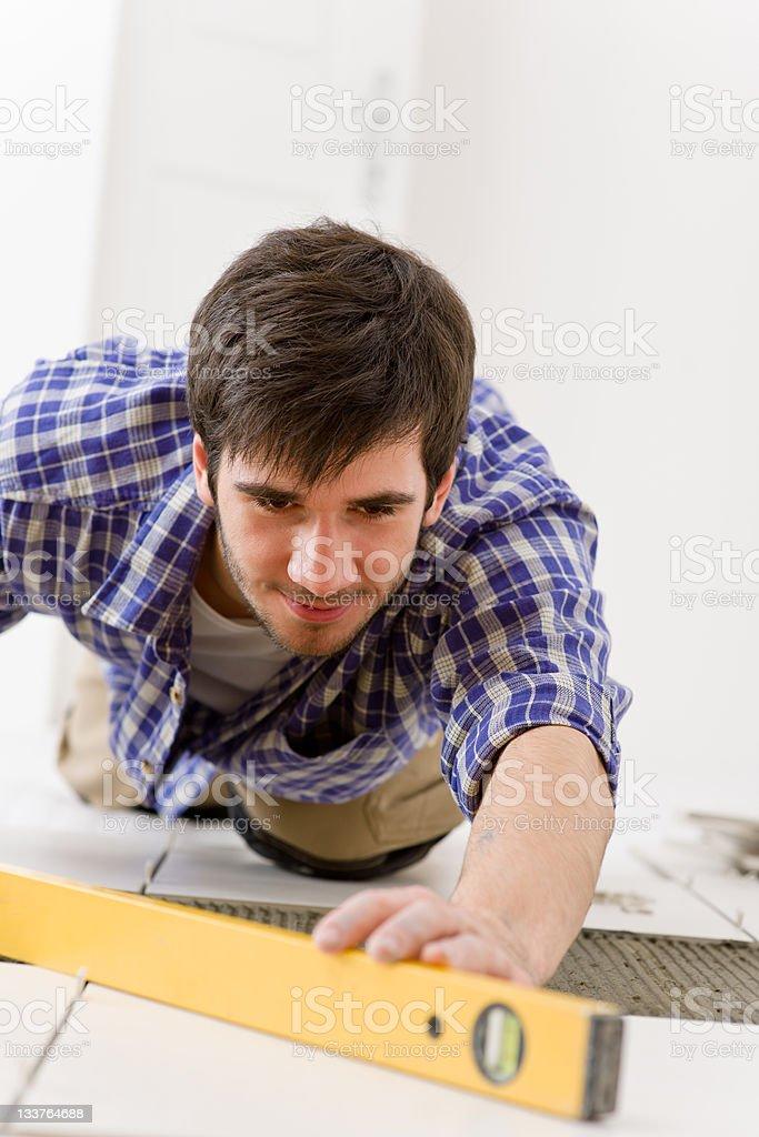 Man using level to do home improvement stock photo
