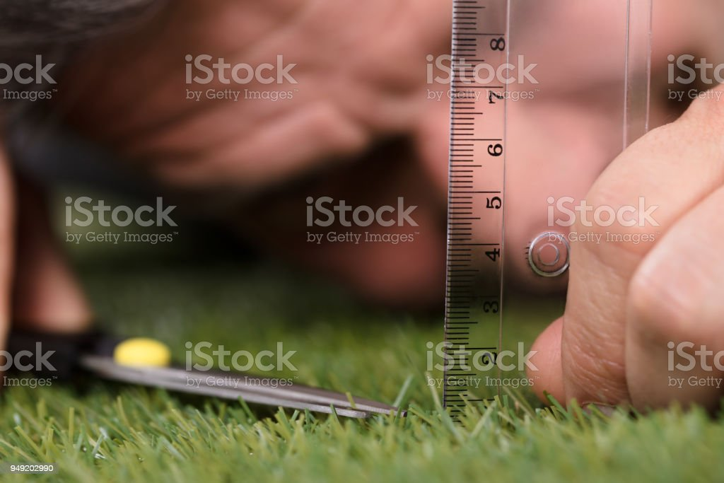 Man Using Measuring Scale While Cutting Grass stock photo