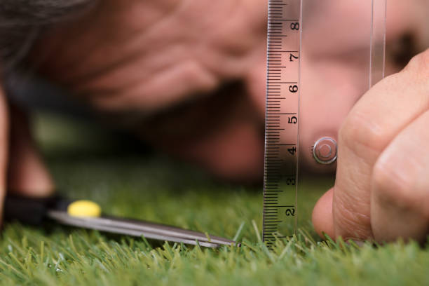 man using measuring scale while cutting grass - perfection stock pictures, royalty-free photos & images