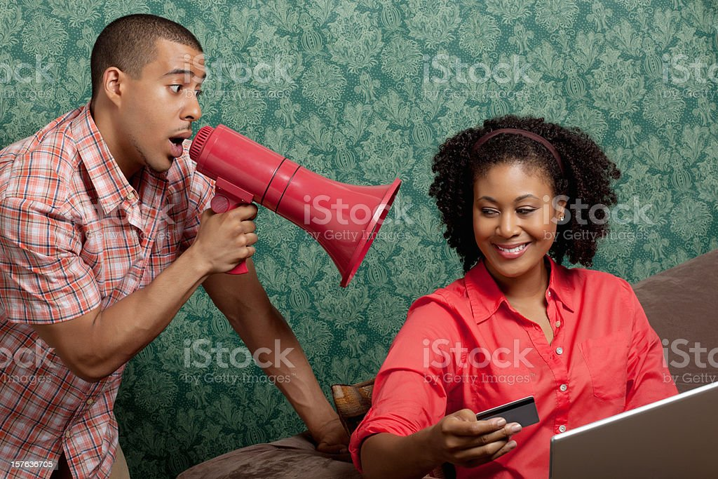 Man using megaphone as woman shops online at home royalty-free stock photo