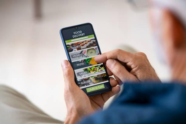 mann mit mobiler app, um liefernahrung zu bestellen - bestellen stock-fotos und bilder
