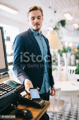 istock Man using Mobile Payment System 814541228