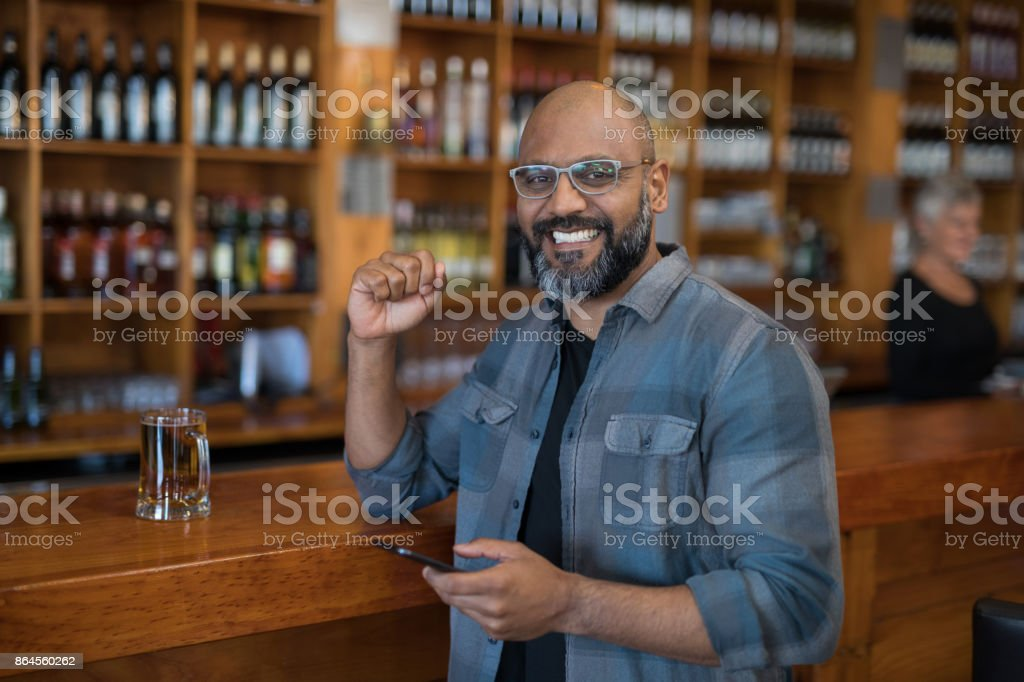 Man using mobile phone at counter in bar stock photo