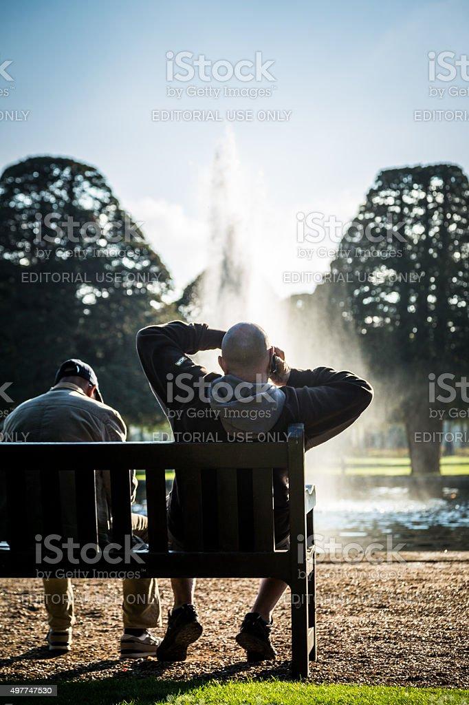 Man using mobile phone at Hampton Court, London, UK stock photo