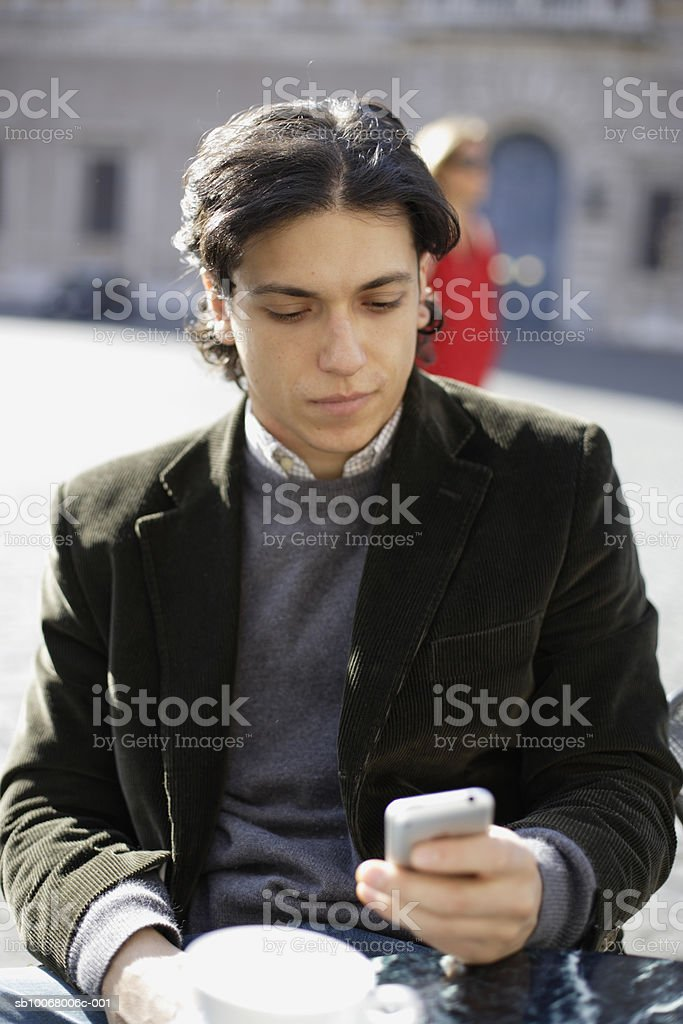 Man using mobile phone at outdoor cafe foto de stock libre de derechos