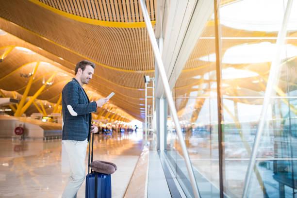 man met mobiele telefoon op de luchthaven op zoek via het venster - airport pickup stockfoto's en -beelden