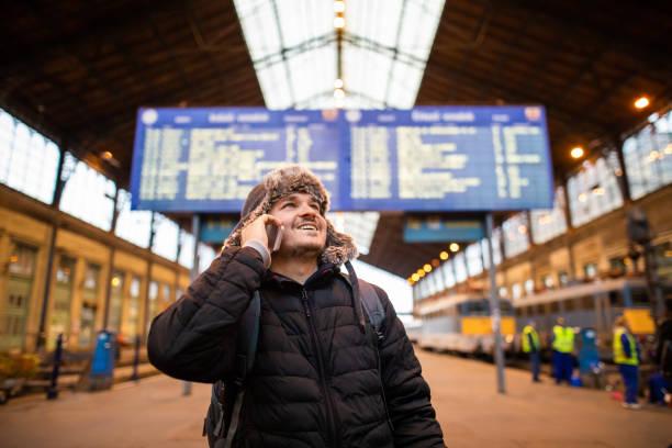 man använder mobiltelefon train station - waiting for a train sweden bildbanksfoton och bilder