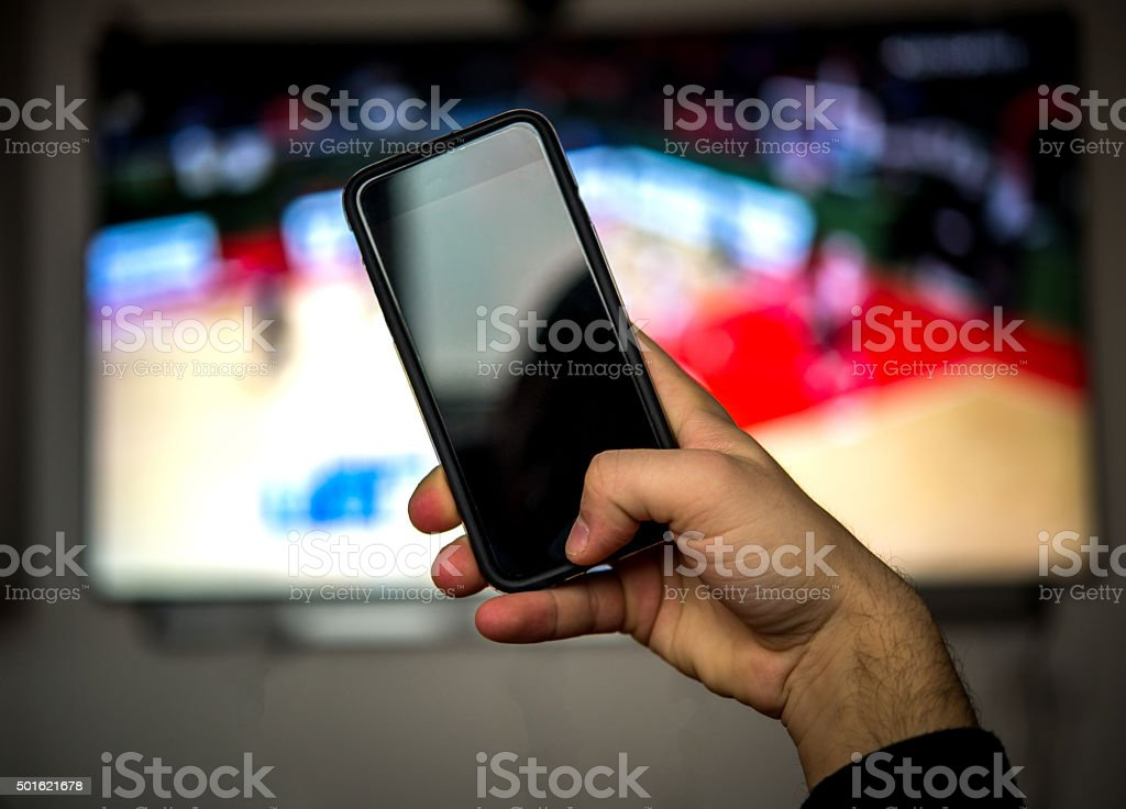 Man using mobile phone during a basketball match stock photo
