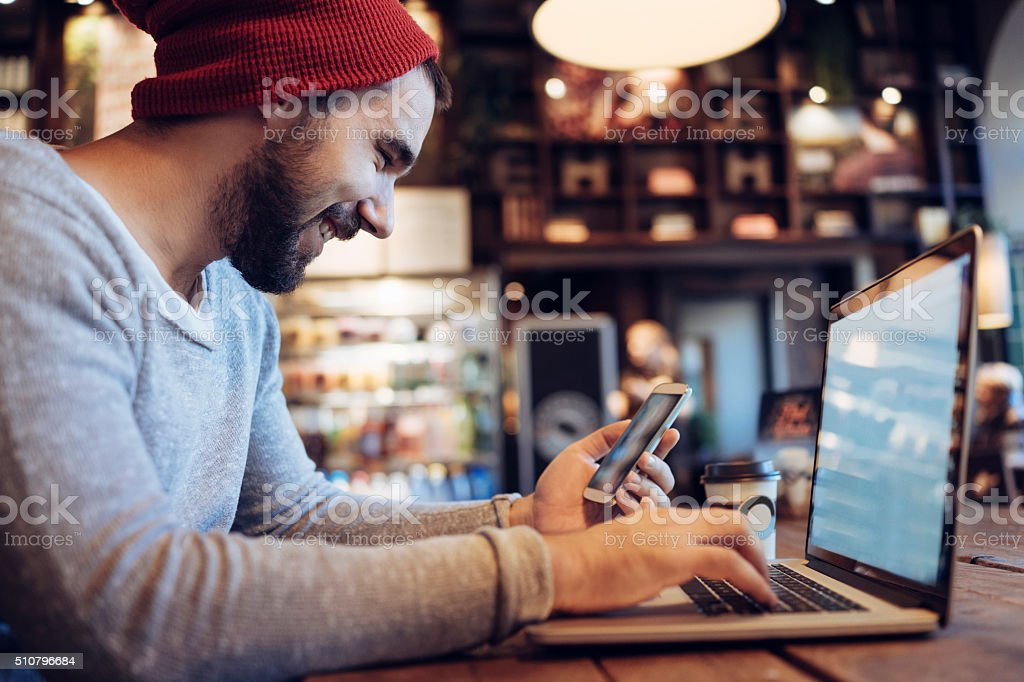 Man using mobile phone in cafe stock photo