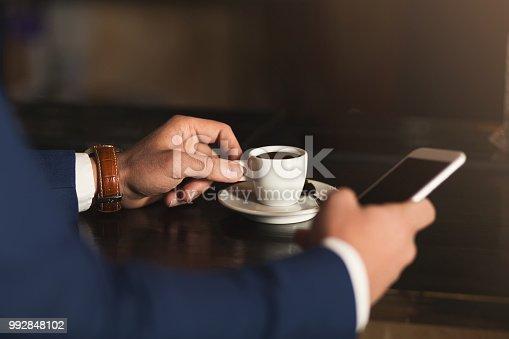 istock Man using mobile phone in coffee bar 992848102