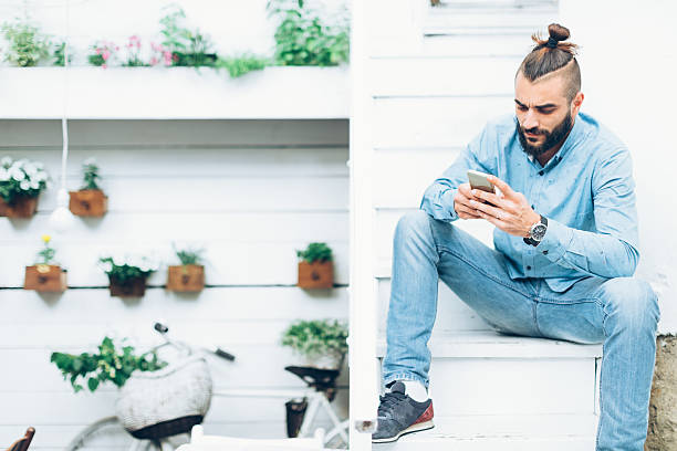 Man using mobile phone Man with beard sitting at the stairs and using mobile phone man bun stock pictures, royalty-free photos & images
