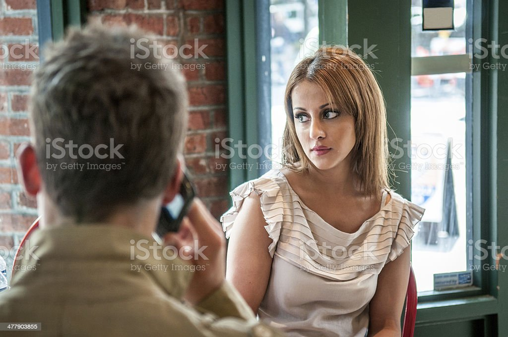 Man using mobile phone while on a date stock photo