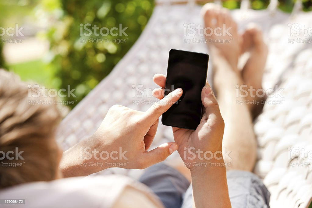 Man using mobile smart phone while relaxing in a hammock stock photo