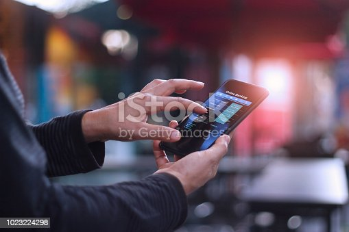 istock Man using mobile smartphone for online banking in cafeteria 1023224298